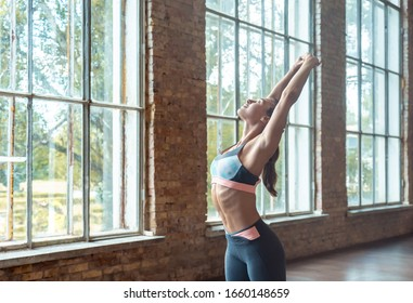 Sporty young woman yoga fitness instructor stretch hands bend back warm up before training keep fit exercise practice work out modern gym fitness studio classroom healthy lifestyle concept copy space.