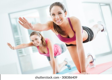 Sporty young women at the gym doing pilates workout on a mat, fitness and healthy lifestyle concept