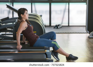 sporty young women sit treadmill in gym