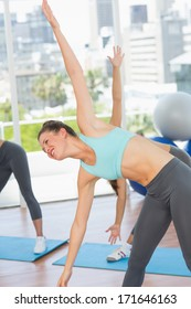 Sporty young women stretching hands at yoga class in fitness studio