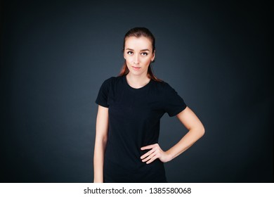 sporty-looking girl in a black T-shirt and leggings on a dark background