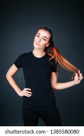 sporty-looking girl in a black T-shirt and leggings on a dark background holding herself by the hair