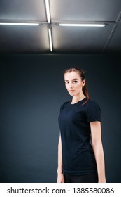 sporty-looking girl in a black T-shirt and black leggings on a dark background and the ceiling with lamps stands confidently and looks into the camera.