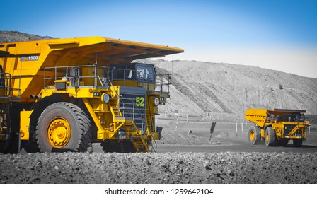 Spot color trucks, two large yellow truck used in a modern coal mine in Queensland, Australia. Trucks transports coal from open cast mine. Fossil fuel industry, Environmental challenge. Logos removed.