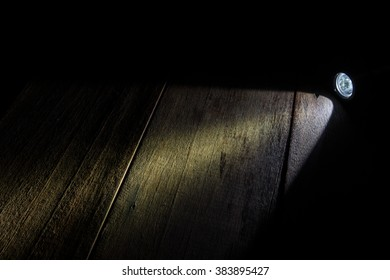 spot flashlight beam on wood bckground