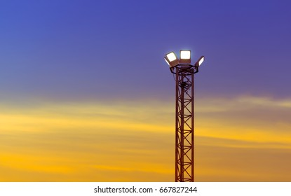 Spot lights pole with blue and orange yellow color light on twilight sky