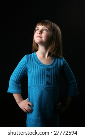 spotlight on the face of pretty young girl in blue dress