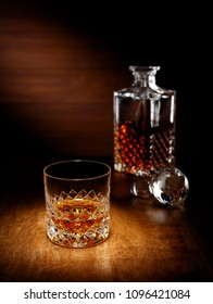 A spotlight on a single crystal glass of scotch whisky with a decanter in the backghround, shot on a wooden table top.