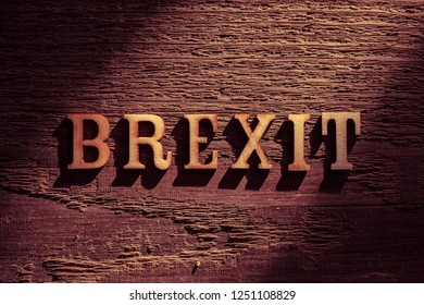 spotlit overhead photo of wooden word BREXIT on wood surface