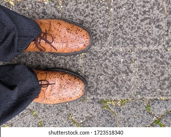 Spots show on men's brown leather (or camel color) dress shoes after rain. Perspective view of man looking down at his feet on a surface of pavers with grass.