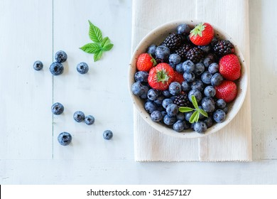 Spotted ceramic bowl with assortment berries blueberries, strawberries and blackberries at white textile napkin over wooden table. Natural day light. Top view