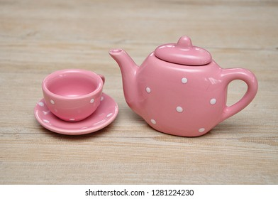 A spotted pink porcelain tea cup and kettle on a wooden background