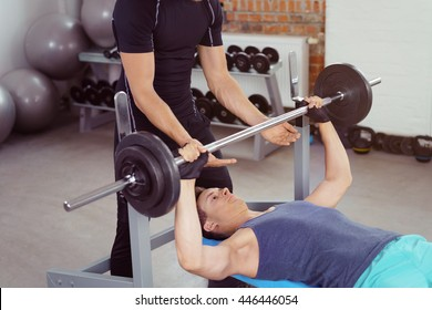 Spotter in black helping young man in blue shirt and pants during barbell training with other weights and stability balls in background
