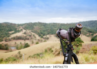 spotting scope or monocular on blurred green mountain as background
