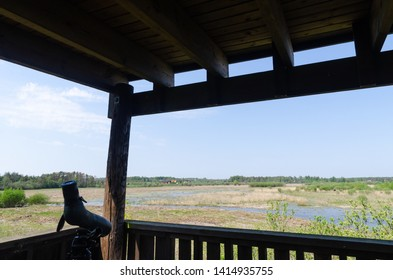 Spotting scope on a tripod in a bird watching tower with view over a wetland at the swedish island Oland