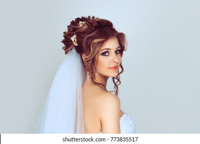 Spouse looking back. Beautiful young bride. Stylish woman fiancee with bridal hairstyle, event makeup and jewelry. Isolated light blue background with copy space