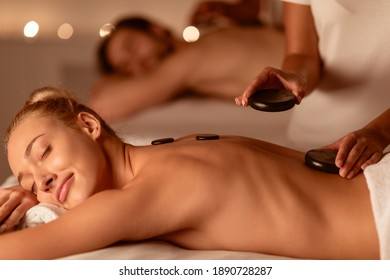 Spouses Relaxing Receiving Exotic Hot Stones Massage Lying On Beds Indoors. Spa Relaxation Concept. Wellness And Body Care Treatment Concept. Selective Focus, Low Light