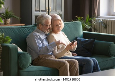 Spouses sitting on sofa grey haired husband help to wife with electronic device cellular usage, elderly couple discuss new application browse internet together older generation and modern tech concept