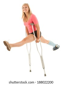 A sprained ankle can't keep this cheerful woman down. She is doing a split on crutches. Studio shot, isolated on white background.