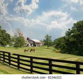Sprawling acreage of pastures surround a horse farm in Kentucky, USA.  Two horses graze in the pasture with an old rustic barn and silo in the background.