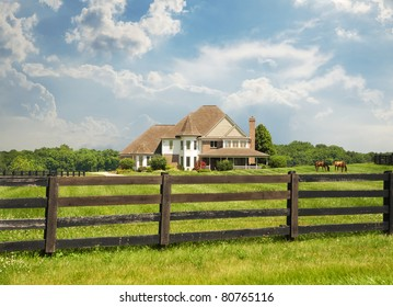 Sprawling green pastures and a wood fence surround a horse farm in Kentucky, USA.