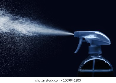 spray bottle - lighted while spraying on dark background