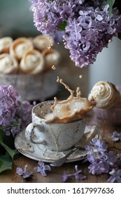 Spray in a cup of cappuccino and cake horns from puff pastry with vanilla cream in a metal box in spring still life with a bouquet of lilacs on a wooden table