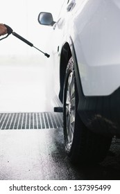 Spray gun, held by hand, used to wash a white off-road car, splashing water, shiny background, vertical, half of car, on gas station, wheel detail, low perspective