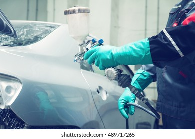 spray gun with paint for painting a car