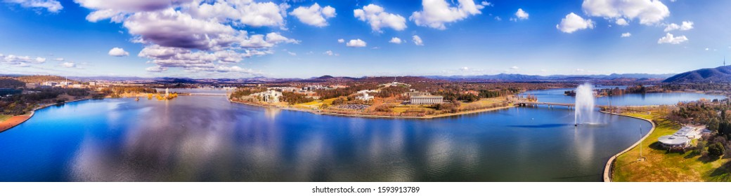 Spray of mighty water fountain in the middle of Lake Burley Griffin in Canberra - Australian capital city. WIde aerial panorama over cityscape on a sunny day.