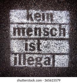 "Spray painted graffiti on sidewalk with words ""Kein Mensch ist illegal"" written in German (No Person is Illegal)"