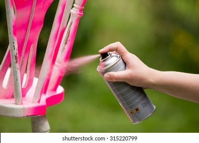 Spray painting an old chair in the color pink