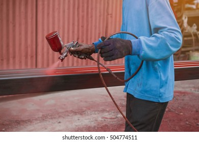 Spray painting red color to the steel by the worker
