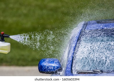 The spray pattern of a pulsating pressure washer spraying soapy water onto a blue car.