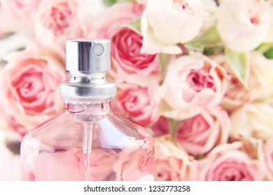 Spray perfume bottle closeup, pink rose blossom soft light background.