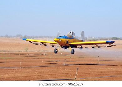A spray plane or crop duster applies chemicals to a field of crops.
