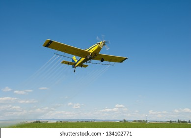 A spray plane flies over a farm and fields on the High Desert of Idaho.