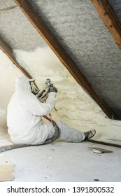 spray polyurethane foam for roof - technician spraying foam insulation using plural component gun for polyurethane foam, inside