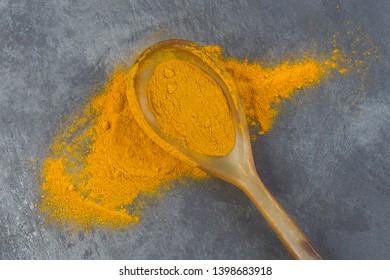 Sprayed spoon of tumeric spreaded on a table