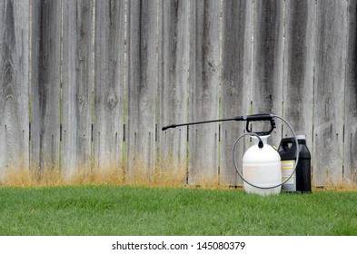 Sprayer and Chemicals in front of Fence