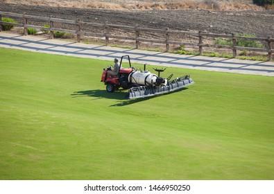 Sprayer machine performing maintenance at golf course. Shelf propelled vehicle