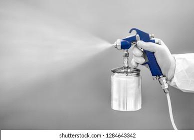 敷地の塗装や塗り潰し用の噴霧器。防護服を着た男性の手にスプレータンクを接写する。