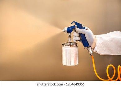 Sprayer for painting or dizenfection of premises. Closeup spray tank in the hand of a man in a protective suit.
