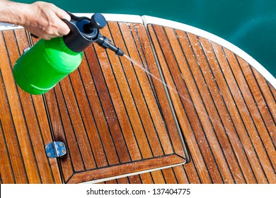 Spraying cleaning solution on deck of boat.