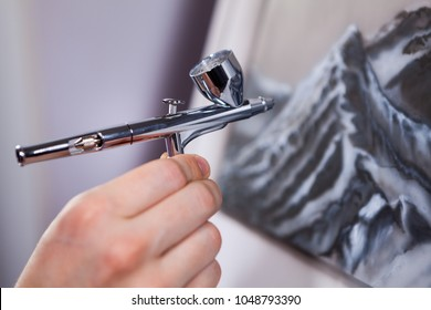 Spraying gun an air brush in female hand, painting mountains with aerograph, close-up view