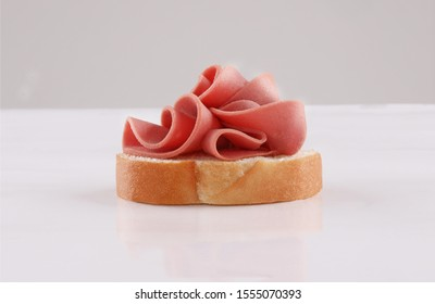 spread cheese, mortadella, sliced ham on slices of baguette, french canape, spanish tapas with herbs on white background