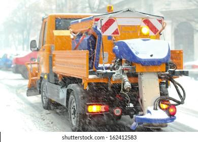 Spreader truck in winter snow blizzard weather