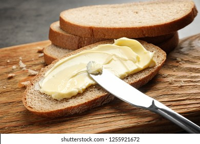Spreading butter onto toast with knife on wooden board