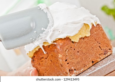 Spreading cream on christmas cake icing with spatula