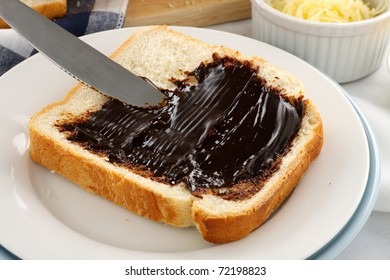Spreading the iconic Australian spread vegemite on to a slice of fresh bread.